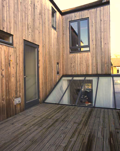 K glass panels. Softwood decking laid on top of a stainless steel warm roof.
